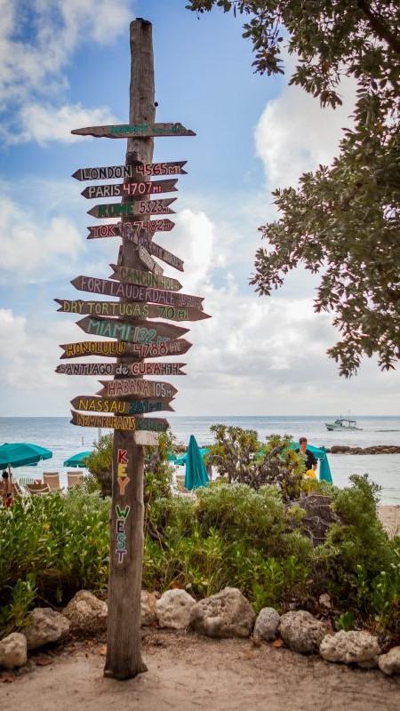 Key West wooden pole with mileage signs to worldwide destinations.